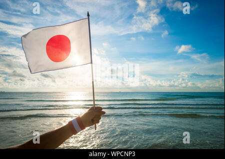 Hand with Japan red and white wristband holding a Japanese flag waving in front of golden sunrise scene at the beach - Stock Photo