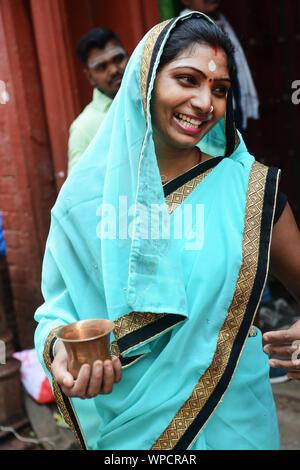 A beautiful Indian woman wearing a colorful Sari. - Stock Photo