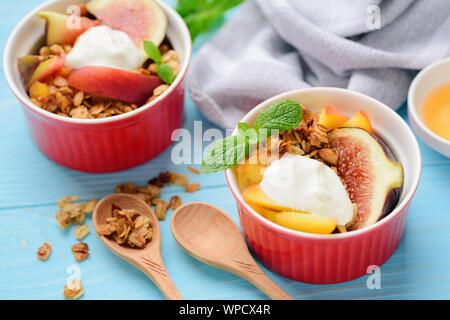 Fruits with granola and greek yogurt cream. Peach, fig honey crisp. Healthy dessert - Stock Photo