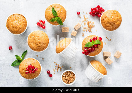 Vegan homemade muffins decorated with red berries and mint leaf on bright grey concrete background. Top view. Homemade tasty muffins - Stock Photo