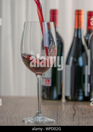 Elegant glass cup filled with red wine, two bottles of wine in the background blurred on a wooden table. - Stock Photo