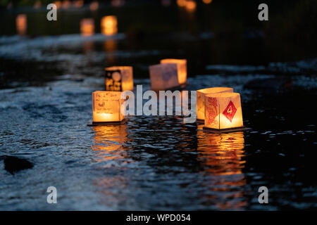 Many water Lanterns float downstream from people releasing them at Pamperin Park in Green Bay, Wisconsin - Stock Photo