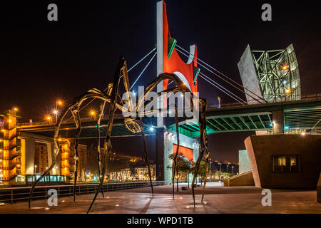 Night view of Maman giant spider sculpture on the walkway of Guggenheim Museum with La Salve Bridge in the background, Bilbao, Basque Country, Spain - Stock Photo