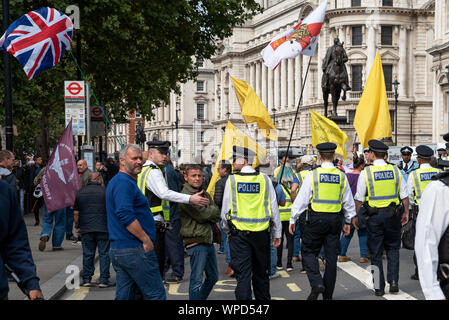 London, UK. 7th September 2019. Demand Democracy Johnson Out - Stop The Coup demonstration. Protestors massed in Whitehall  near the gates of Downing Street. Met police move on and escort right wing yellow vest activists away from Whitehall. Hosted by Another Europe is Possible, Green Party of England and Wales, Momentum, Stop Trump, Owen Jones and Labour for a Socialist Europe. Credit: Stephen Bell/Alamy - Stock Photo