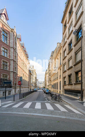 Old Paris street with high-rise residential brick buildings of classical architecture with commercial premises on the ground floor and cars standing o - Stock Photo