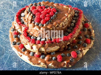 Raw healthy vegan multi-story cheesecake, made in heart form, laid on blue background. Top view. - Stock Photo