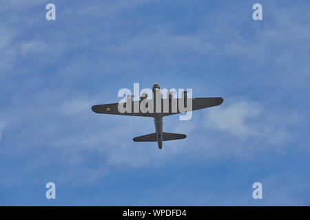 Under side view of the WWII bomber the Boeing B-17 Flying Fortress while flying over the top against a blue sky with some clouds - Stock Photo