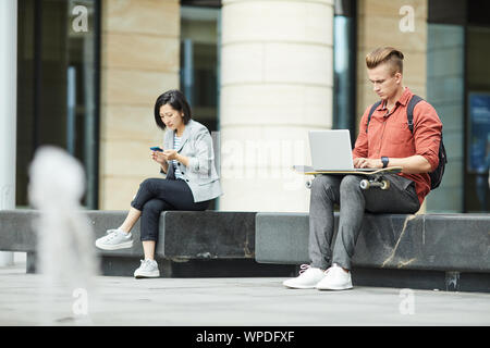 Full length portrait of two young people using electronic devices while siting on bench outdoors in urban setting, copy space - Stock Photo