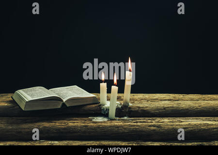 Beautiful open bible and burned candles on a old oak wooden table and dark background. - Stock Photo