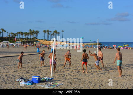 group of young men playing beach volleyball on the Arenal Beach in Javea on the Costa Blanca, Spain.  Late afternoon in the summer - Stock Photo