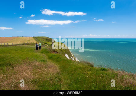 A couple walks along the North Downs Way a top of the White Cliffs of Dover, Kent. - Stock Photo