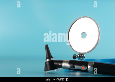 Otoscope with reflector mirror on blue background in health care concept. - Stock Photo