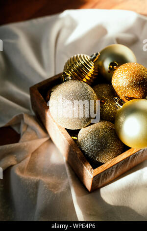 Christmas or New Year preparation.Various vintage gold Christmas tree decoration toys or balls in a wooden box on the floor.Festive holiday mood - Stock Photo