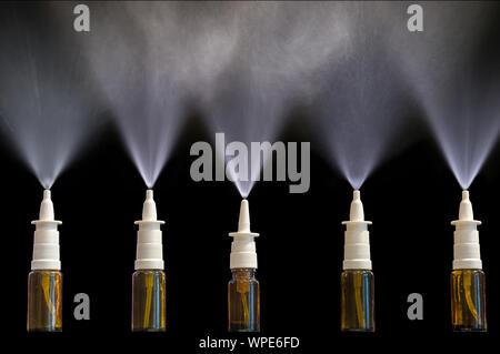 Spraying nasal sprays in front of black background - Stock Photo