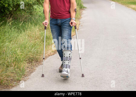 Walking exercises with crutches and an orthosis on the lower leg - Stock Photo