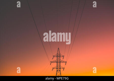 Electric power lines in the evening sun. Electric energy transmission pole in vibrant background, concept of electricity