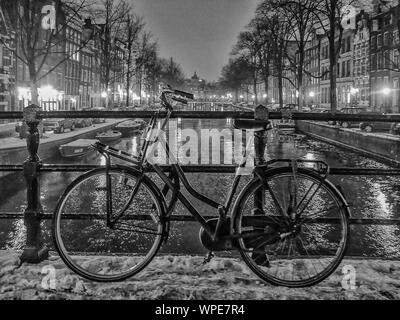 Full Length Of A Parked Bicycle On Railing Against Canal - Stock Photo