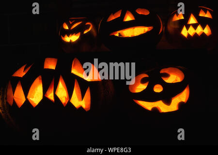 Various creatively carved pumpkins in the dark for Halloween - Stock Photo