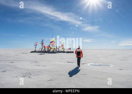 Young man walking to the international flags from different countries in Uyuni salt flat in sunny day with sun rays, Bolivia, South America travel voc