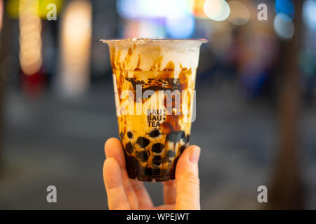 Hand holding plastic cup of Black Sugar Milk Tea (Bubble Tea) with blurry bokeh background (Bau Bau tea) - Stock Photo