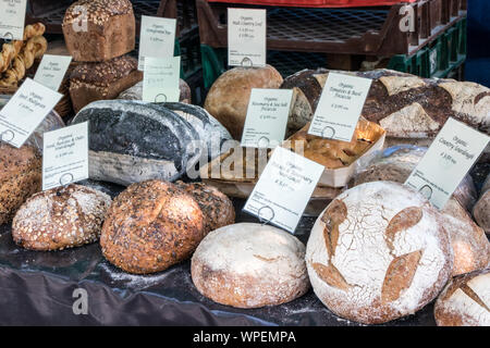 A variety of organic bread on farmers market stall - Stock Photo