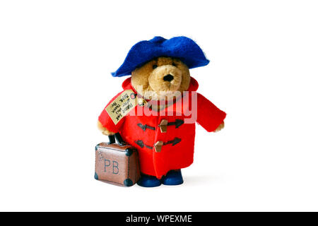 A Paddington Bear soft toy with red duffel coat, blue hat and suitcase, isolated against a white background - Stock Photo