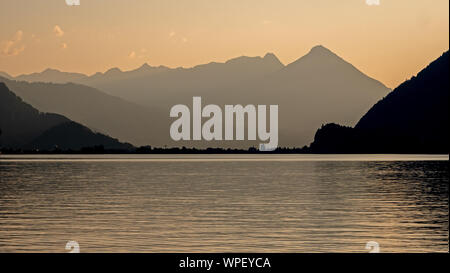 Sunset looking down the lake of Brienz in Switzerland. The high mountains cast a silhouette against the orange sky and reflections in the water of the - Stock Photo