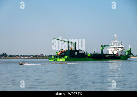 Stadersand, Germany - August 25, 2019: Hopper Dredger Schwedt River deepening the fairway on Elbe River at hazy day. - Stock Photo