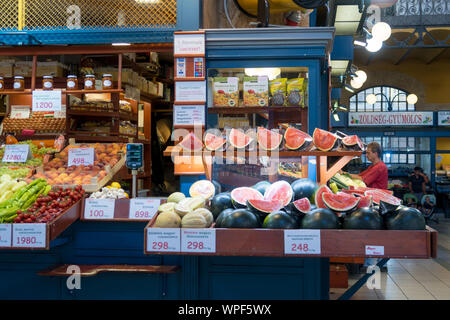 Budapest, Hungary - Aug 16, 2019: Colourful fruit stall with melons and fruits in the covered Central Market Hall in Budapest, Hungary - Stock Photo