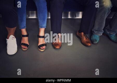 Low Section View Of Passengers In Subway Train - Stock Photo