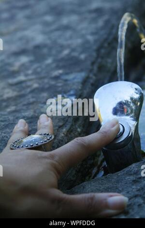 Cropped Hand Of Woman Pressing Faucet Button - Stock Photo