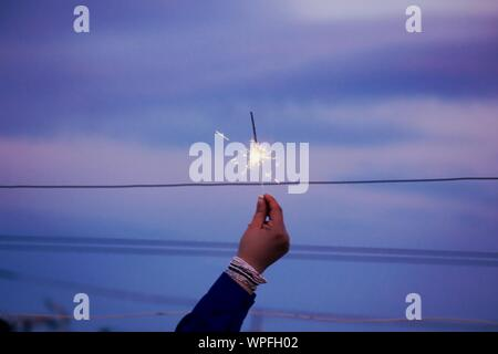 Close-up Of Hand Holding Diwali Cracker Against The Sky - Stock Photo
