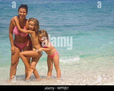Portrait Of Happy Mother With Daughters At Beach - Stock Photo