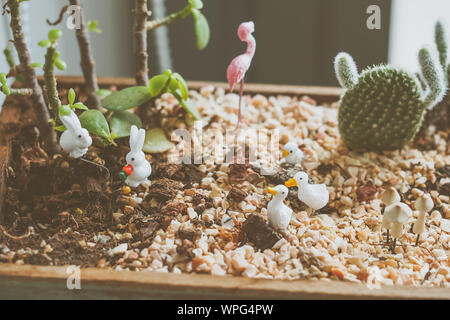 Close-up Of Figurines And Pebbles In Window Box - Stock Photo