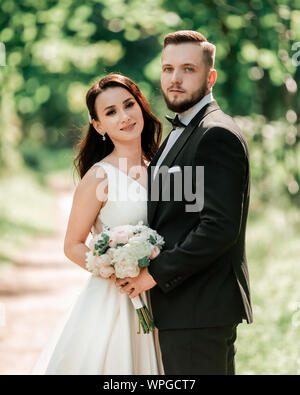 happy bride and groom standing under the wedding arch - Stock Photo