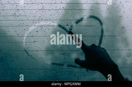 Cropped Image Of Person Drawing Heart Shape On Wet Glass - Stock Photo
