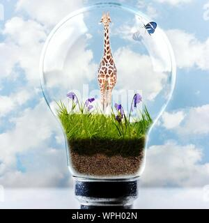 Digital Composite Image Of Giraffe On Flower Plants In Electric Bulb Against Sky - Stock Photo