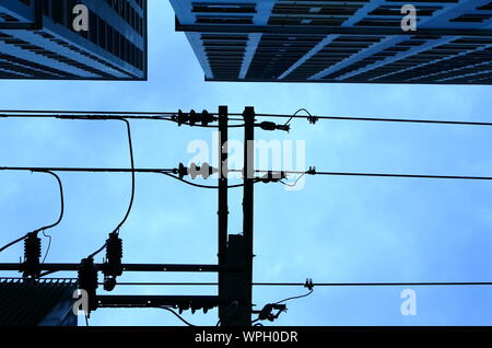 Closeup silhouette picture of high voltage power lines installing on high electric post near the building with blue sky background just after raining, - Stock Photo