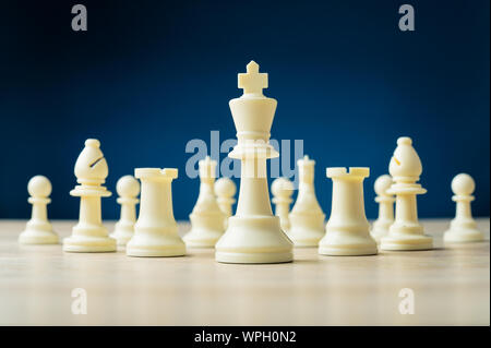 White chess pieces with the king as the leader placed on wooden desk in a conceptual image. Over blue background. - Stock Photo