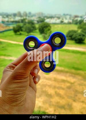 Cropped Hand Of Man Holding Fidget Spinner Over Field - Stock Photo