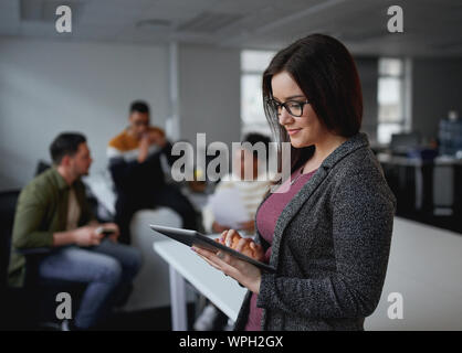 Happy young businesswoman using digital tablet in office and colleagues discussing in background
