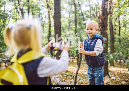 Children preschoolers Caucasian brother and sister take pictures of each other on mobile phone camera in forest park autumn. theme of hobby and active