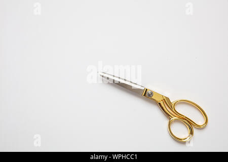 Scissors closed gold and silver color isolated against white background, copy space, top view. Tailor, barber concept - Stock Photo