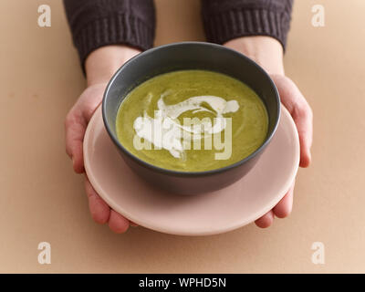 Pea soup in hands - Stock Photo