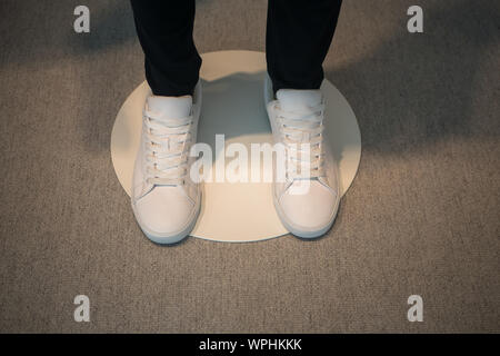 Window display of a male mannequin wearing white shoes. - Stock Photo