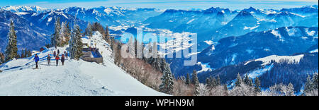 ST GILGEN, AUSTRIA - FEBRUARY 23, 2019: Panorama of hazy snowy Alps and Wolfgangsee lake from the top of Zwolferhorn mount with a view on skiers, goin - Stock Photo
