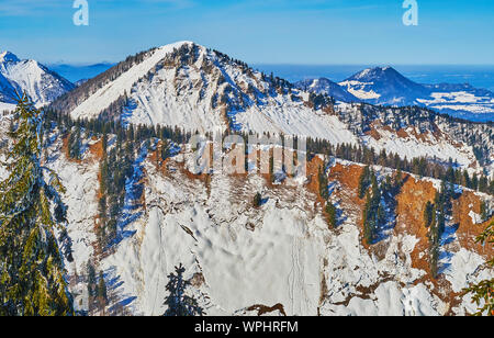The view on great snowy Alps of Faistenau with steep slopes and spruce trees, stretching along the top, seen from the  Zwolferhorn mount, St Gilgen, S - Stock Photo