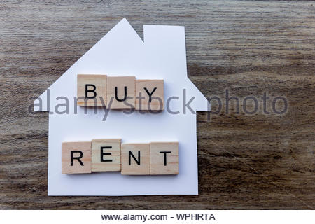 Housing Market Concept - Paper house with the words 'Buy, Rent' - Stock Photo