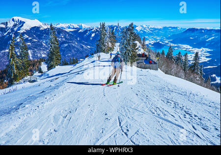 ST GILDEN, AUSTRIA - FEBRUARY 23, 2019: The single skier makes downhill from the peak of  Zwolferhorn mount with a view on Alpine scenery and Wolfgang - Stock Photo