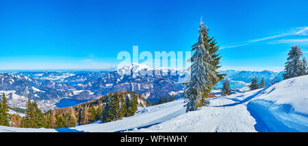 Panoramic view from Zwolferhorn mount on its snowy slopes, valley of Wolfgangsee lake, old spruce trees and rocky Alps, St Gilgen, Salzkammergut, Aust - Stock Photo